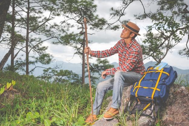 男性は座って、熱帯林の山々をバックパックで眺めます。冒険、旅行、登山。