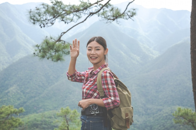 少女はジャングルの中でバックパックと一緒に熱帯林の丘の頂上で手を振った。アドベンチャー、ハイキング。