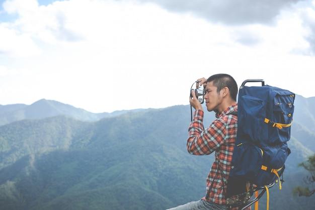 若い男が、森のバックパックと一緒に熱帯林の山頂の写真を撮ります。冒険、旅行、ハイキング。