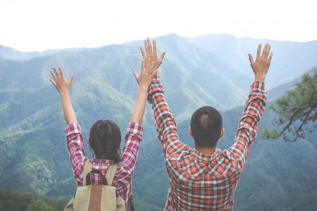 カップルは、熱帯林の丘の上で両手を上げました。ハイキング、旅行、登山。
