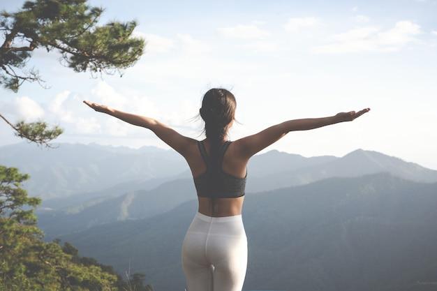 彼の上に瞑想と運動の美しい若い女性。
