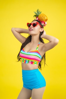 Красивая женщина в купальнике держит ананас позирует на желтом