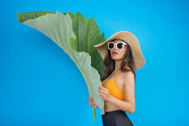 青に緑の葉のポーズを保持している水着の美しい女性