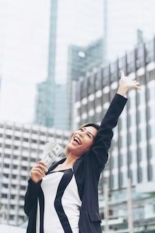 Успешная красивая азиатская бизнес-леди держа деньги долларовые банкноты в руке, концепцию дела