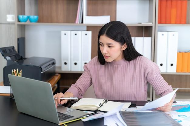 若い美しいオフィスのテーブルの上のノートパソコンでの作業