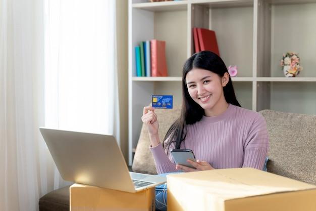 若い女性はオンラインショッピングのための手でクレジットカードを表示します