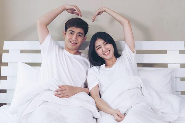 幸いなことに若いカップルが腕を上げるハートを作る