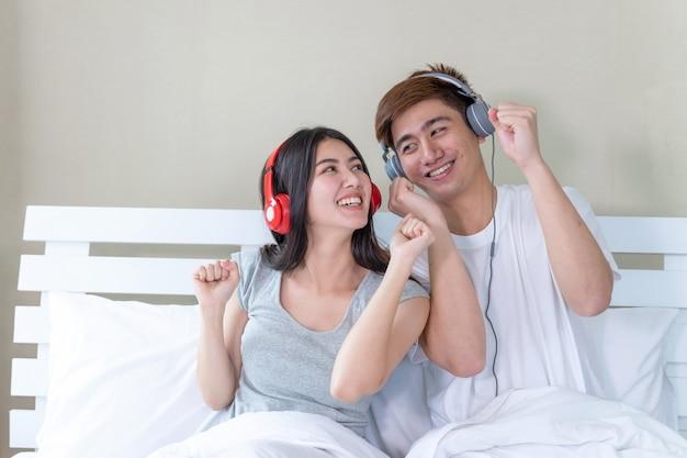 若いカップルのリスニングとイヤホンからの音楽とダンス