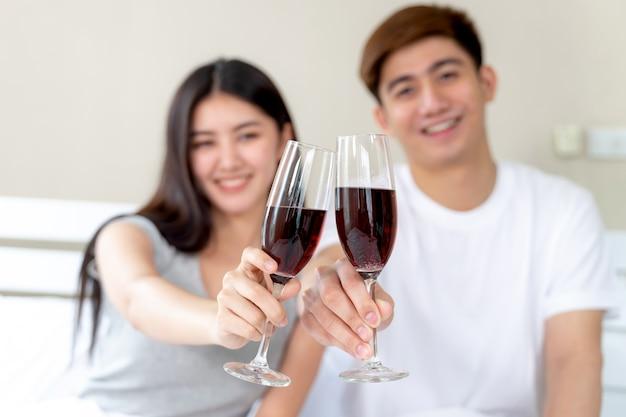 寝室でワインのグラスを保持している若いカップル