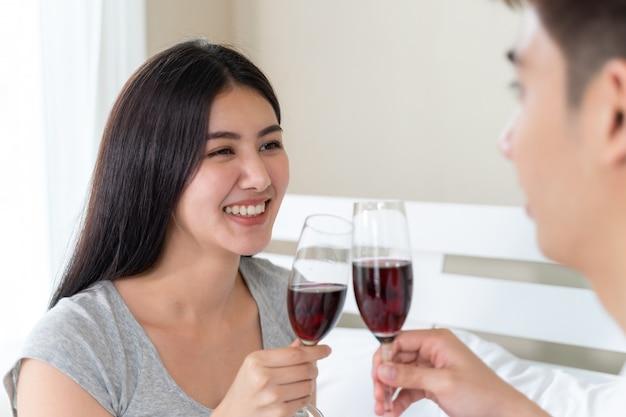 若いアジアカップルは、寝室でワインの幸せな持株ガラスを祝うを祝う