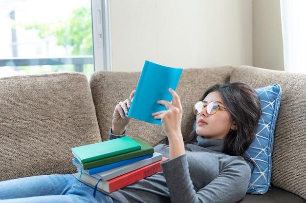 Молодая женщина читает учебник на диване у себя дома