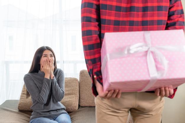 Молодая красивая женщина чувствует себя захватывающе, чтобы получить подарок от парня
