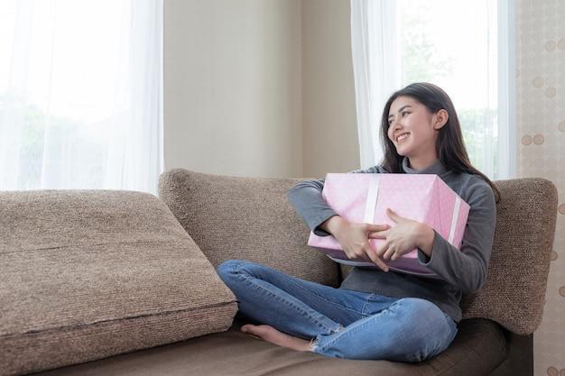 Симпатичная женщина смайлик и обнять подарок со счастливым