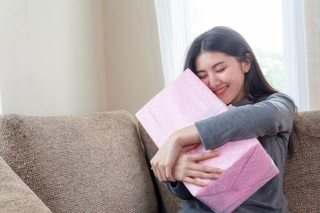 Симпатичная девушка чувствует себя счастливо и обнимает розовый подарок на диване, смотрит вперед и улыбается