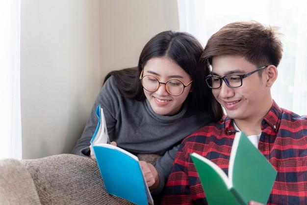 ソファに座って本を読んで愛する若いカップル