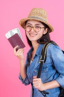 麦わら帽子をかぶっている女性旅行者は紙幣とパスポートを保持しています。