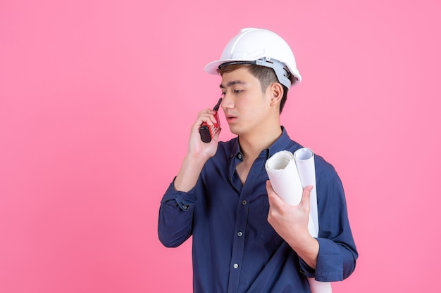 Портрет молодой архитектор человек в белом шлеме и держит мегафон в руке