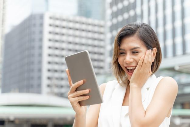 ライフスタイルビジネスの女性は、スマートフォンを使用して幸せを感じる