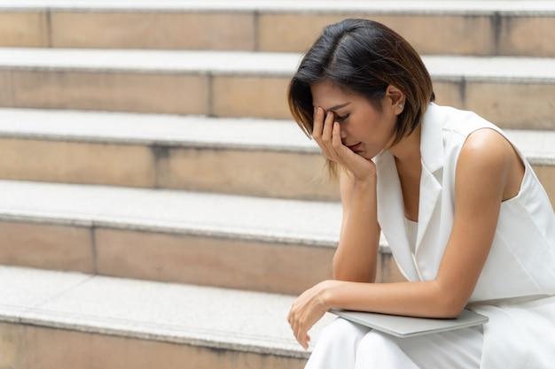 階段で泣いている悲しみの若い女性
