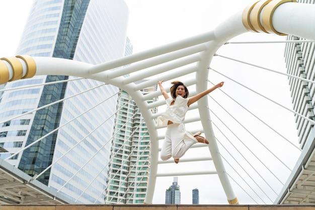 ライフスタイルビジネスの女性は、成功を祝う空気で幸せなジャンプを感じる