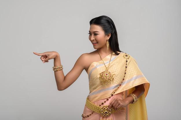 Женщины носят символические тайские костюмы, указывая пальцами