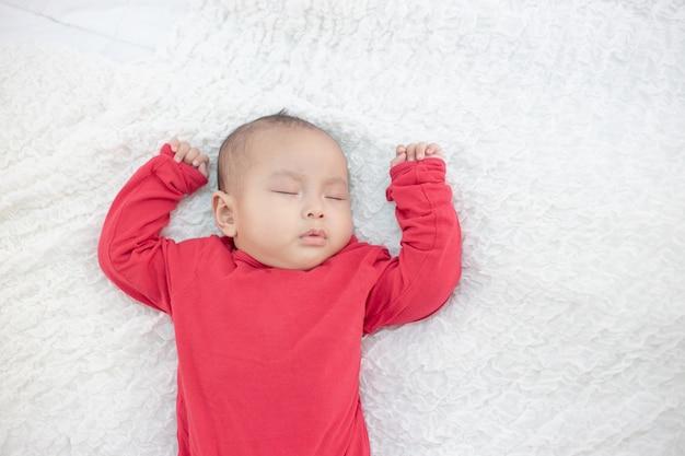 ベッドで寝ている赤いシャツを着た赤ちゃん