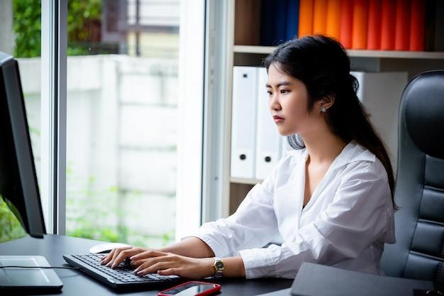 Молодая работница печатает на клавиатуре компьютера