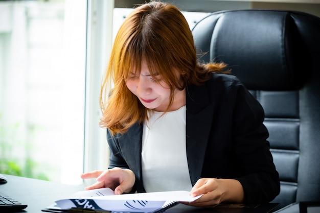 書類を確認しながら深刻な若い上司