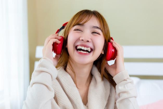 女の子はヘッドフォンを着てベッドで音楽を楽しんでいた