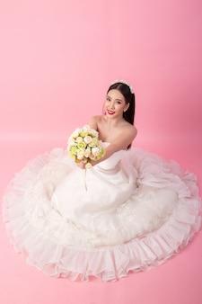 ピンクのスタジオで美しいアジアの花嫁の肖像画