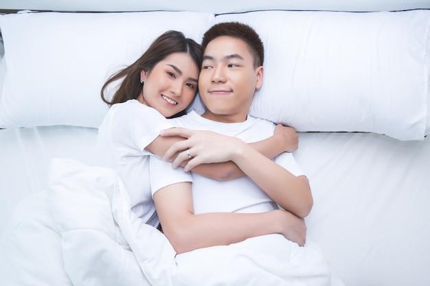 Счастливая азиатская пара на кровати у себя дома