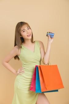 Красивая азиатская женщина с хозяйственной сумкой и кредитной карточкой в руке