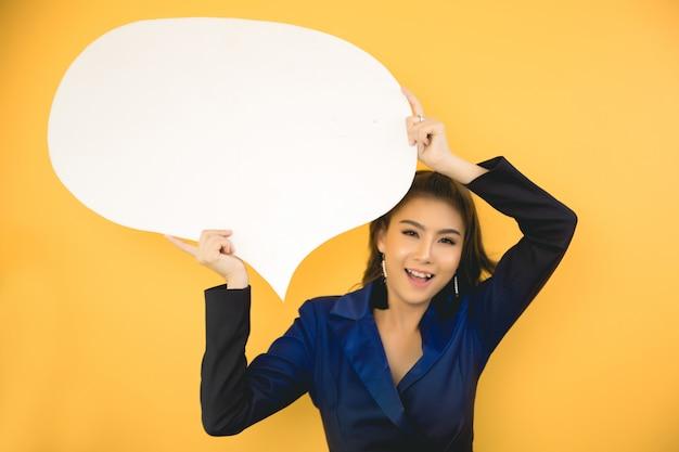Азиатская женщина держа и смотря вверх к пузырю речи с пустым космосом для текста