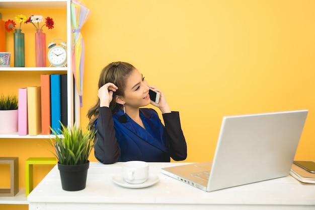 オフィスでラップトップに取り組んでいる陽気なビジネス女性