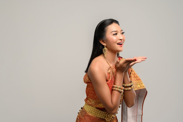 Женщина в тайском платье, которое сделало символ руки