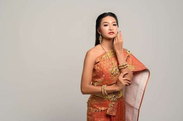 Женщины носят тайскую одежду и руки касаются их лица