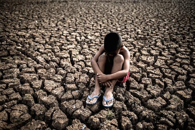 膝を抱いて座っている男性、曲がった、乾燥した土壌で曲がった、地球温暖化
