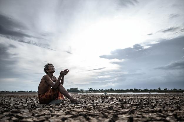 Пожилой мужчина сидел, прося дождя в сухой сезон, глобального потепления