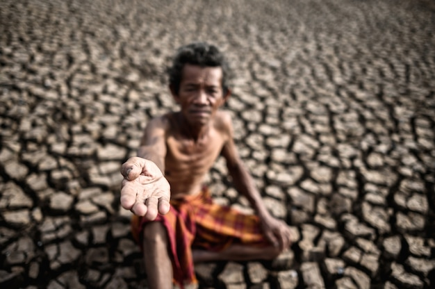 高齢者が乾季に雨を求めて座っていた、地球温暖化