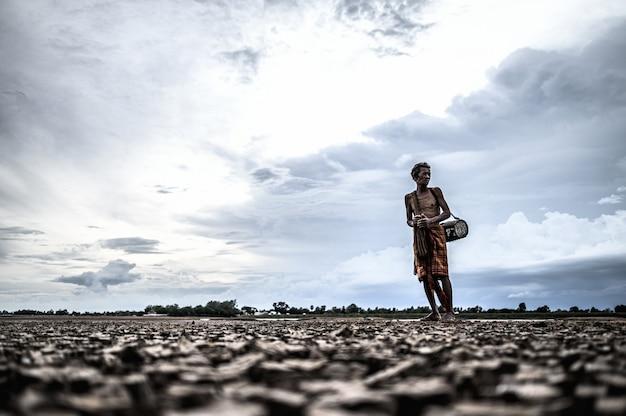 高齢男性は乾燥地で魚を見つけ、地球温暖化