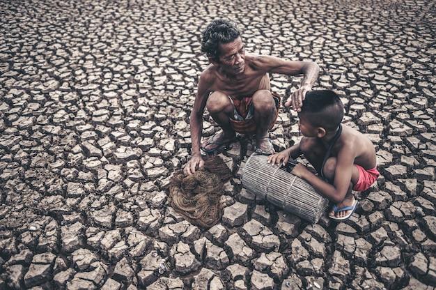 高齢の男性と少年が乾燥した地面で魚を見つけ、地球温暖化