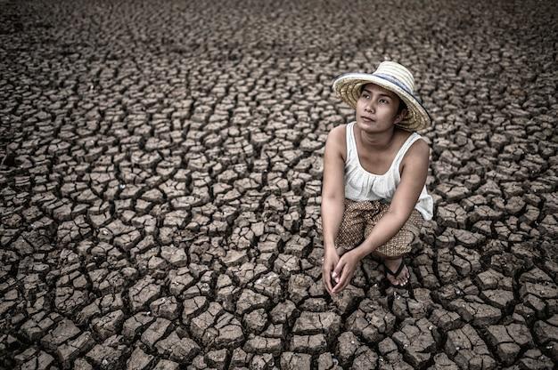 女性は、乾燥した気候と温暖化の中で空を見ながら座っています。
