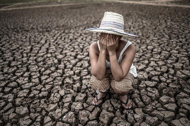 手に座っている女性は、温暖化の世界で乾いた地面で顔を閉じました。