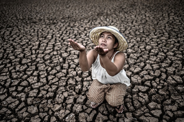 女性は空を見ながら座って、乾燥した天候の中で雨を求め、地球温暖化