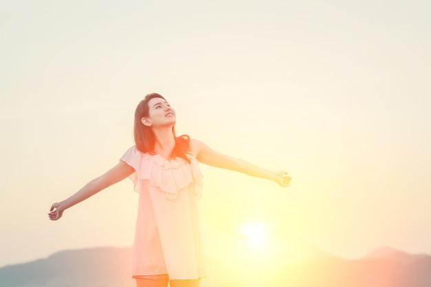 Девушка с руками, вытянутыми и солнце позади