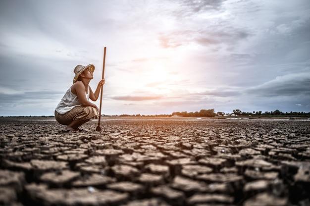 女性は彼の手に座って、乾いた土壌でシェムを捕まえて空を見ました。