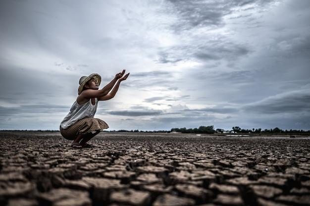 Женщина сидит, прося дождя в сухой сезон, глобального потепления