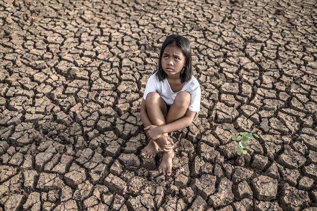膝を抱いて座っている女の子、空を見て、乾いた地面に木がある