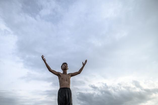 少年は空に手を上げて、雨、地球温暖化、水危機を求めました