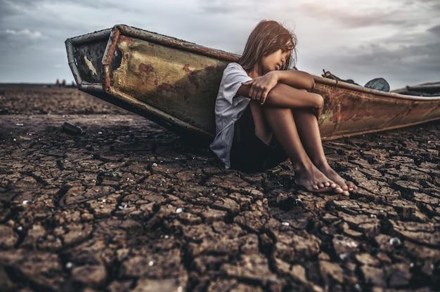膝を抱いて座っている女性は、乾燥した土壌で曲がり、漁船がありました。
